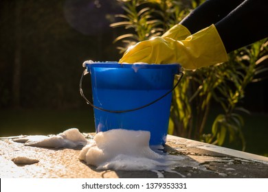 Spring Cleaning outside with big yellow cleaning gloves, water, soap and a big blue bucket with soap. Cleaning the table. Soap Foam on the table. Hands in bucket. Holding and wringing cleaning sponge.