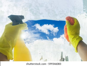 Spring cleaning - someones hands in yellow gloves with spray and ruber cleaning window
