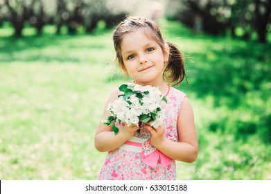 spring closeup outdoor portrait of adorable kid girl. Spending spring holidays in beautiful blooming garden