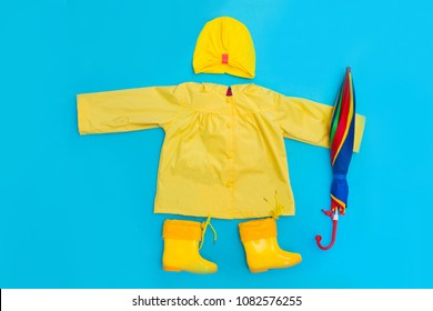 spring clothes on the child and accessories a yellow raincoat, boots and an umbrella on a blue background