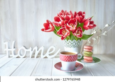 "Spring coffee background. The word ""Home"" made of wood, pink tulips, espresso and macarons, pink and green"