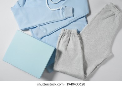 Spring collection. Stylish women clothing lying on light background, gray pants and blue hoodie. Fashion and style concept