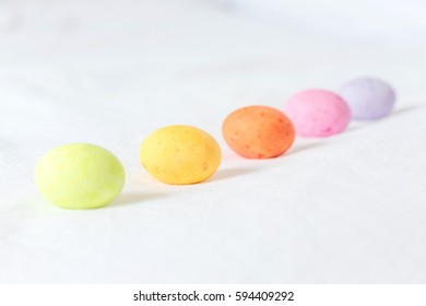 Spring colorful easter eggs sitting in a white sheet forming a diagonal line and white some space between them