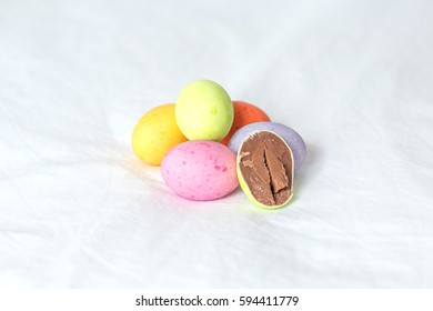 Spring colorful easter eggs sitting in a white sheet with one cutted in half showing it??s milky brown creamy chocolate.