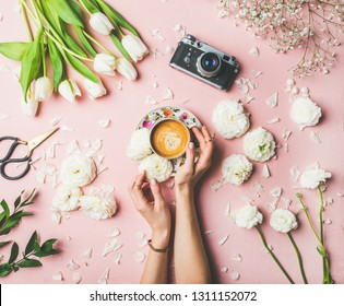 Spring colorful layout. Flat-lay of female hands holding cup of coffee, scissors, film camera, white tulips and buttercup flowers over pink background, top view. Spring or Women's Day holiday concept