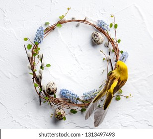 Spring composition with braided wreath of twigs with hyacinth flowers, decorative bird and easter egg