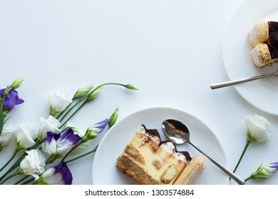 spring composition. Cup of coffee, tiramisu cake, fresh flowers on white background.  Flat lay, top view, copy space