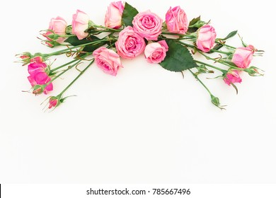 Spring composition with pink roses on white background. Top view. Flat lay. Floral frame of flowers, copy space