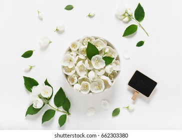 Spring composition with white jasmine flowers on a light wooden background. Wedding invitation card. Copy space. Top view.