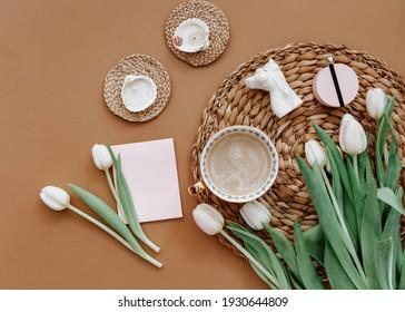 Frühlingszusammensetzung. Weiße Tulpen, Kaffeetasse, Kerze auf braunem Hintergrund. Muttertag, 8. März. Leere Grußkarte. Flach-Lay