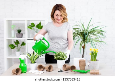 spring concept - portrait of mature woman watering potted plants at home