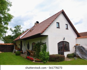 Spring cottage with green grass, side perspective, blue cloudy sky, new roof tiling