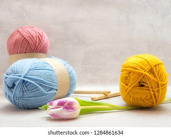 Spring crochet image. Large skeins of wool in blue, pink and yellow. Wooden crochet hooks and a spring flower.