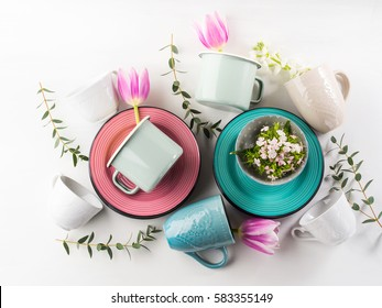 Spring crockery tableware concept with tulips flowers pastel color white background. Textured ceramic plates dishes mugs. Mother woman day gift idea