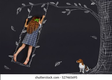 Spring curly girl on a swing. Hand drawing tree on a blackboard. Happy childhood concept.