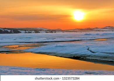 Spring dawn. Bright sun disc in the sky. Among the ice floes there are cracks and water of golden color. The end of May in the Arctic. Anadyr estuary, Chukotka, Far East of Russia. Extreme North.