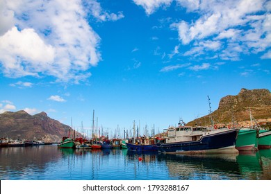 Spring day at Hout Bay Harbour showing fleet of colorful fishing boats at anchor under light clouds and blue sky.