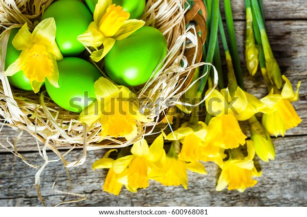 Spring easter background with daffodils and easter eggs in the basket