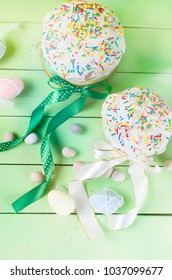 Spring Easter cake with white icing and colorful topping sugar decor and holiday decorations on the bright background
