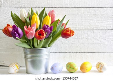 Spring easter tulips in bucket on white vintage planks