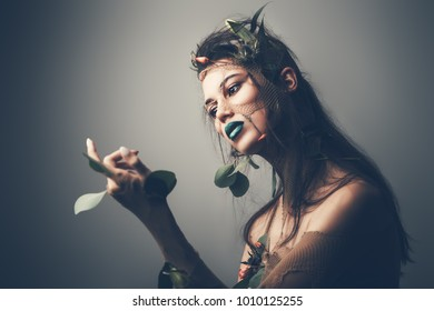 Spring Fantasy. Young woman looks like a beautiful forest nymph with green leaves and bright makeup. Cosmetics and make-up concept.