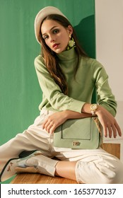 Spring fashion concept: young beautiful fashionable woman wearing green turtleneck, white beret, wrist watch, jeans, cowboy ankle boots, with trendy bag, posing on mint color background.