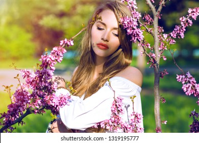 Spring fashion portrait of elegant lady girl with natural long hairs and pretty face wearing trendy elegant white dress, posing around blooming trees, toned bright colors.