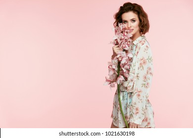 Spring Fashion. Woman With Flowers In Fashionable Clothes. Beautiful Happy Smiling Girl In Trendy Floral Clothing In Pastel Colors With Pink Orchid Flowers Near Face On Pink Background. High Quality