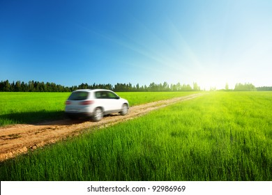 spring field and blured car on ground road