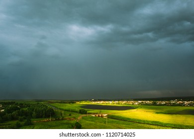 Spring field with green grass with a lake and rain clouds above it. Landscape after the rain with sunspots on the field