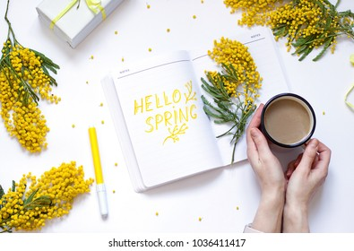 Spring flat lay with yellow flowers, notepad . Woman's hand are holding a cup of coffee. Hello spring concept top view composition