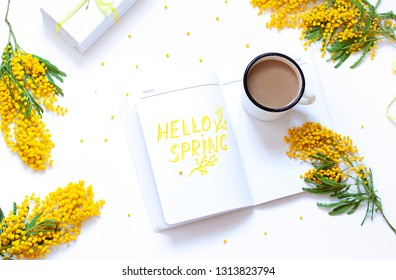 Spring flat lay with yellow flowers, notepad and a cup of coffee. Hello spring concept top view composition