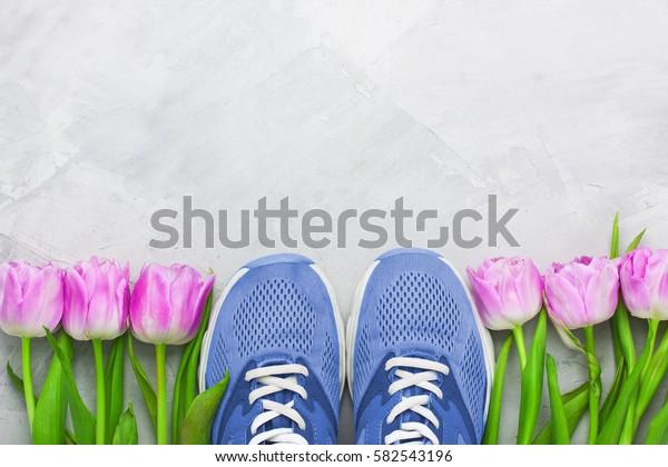 Frühlingsflatlay-Sportkomposition mit blauen Turnschuhen und violetten Tulpen auf grauer Betonhintergrund. Konzept für gesunden Lebensstil, Sport und Ernährung in  Frühling. Horizontale Ausrichtung, Draufsicht.