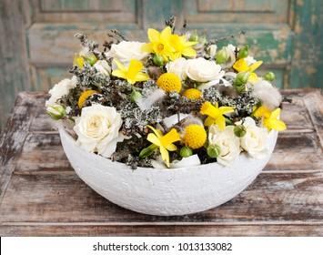 Spring floral arrangement with daffodils and white roses.