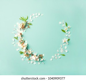 Spring floral background, pattern and wallpaper. Flat-lay of white almond blossom flowers wreath over light mint background, top view, copy space. Womens holiday greeting card or wedding invitation