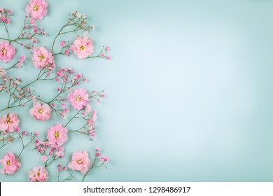 Spring floral composition made of fresh pink flowers on light pastel background. Festive flower concept. Flat lay, top view with copy space.