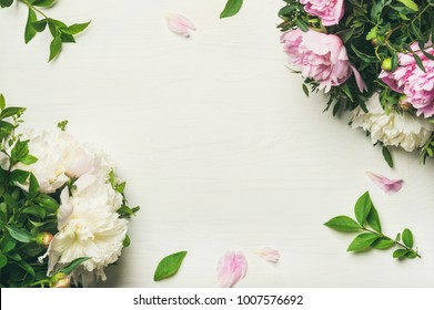 Spring floral layout with flowers. Flat-lay of tender pale pink and white peonies over white background, top view, copy space. Womens day, Valentines or lovers day greeting card or wedding invitation
