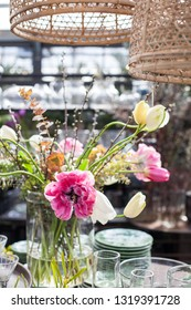 A spring flower arrangement with tulips and cherry twigs in a sunny garden center.