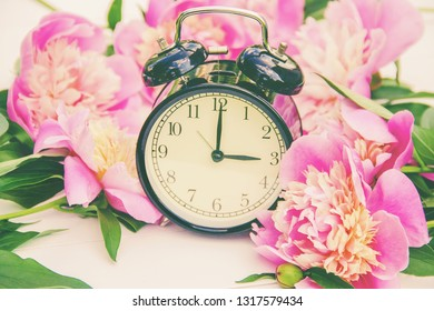 Spring flowers and Alarm Clock. Change the time. nature.