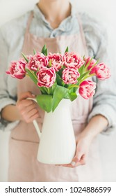 Spring flowers arrangement. Woman in pastel pink apron and blue linen shirt holding white enamel vase with fresh pink tulips. Florist shop, Womans day greeting card concept