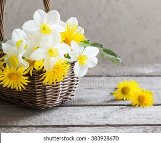spring flowers in basket on wooden background