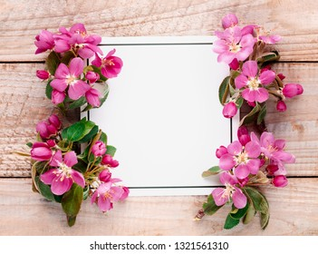Spring flowers and blank card on wooden background
