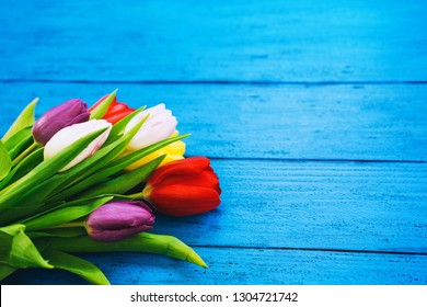 Spring flowers bouquet. Beautiful tulips on rustic wooden bright color turquoise blue background. Flat lay, top view, copy space.