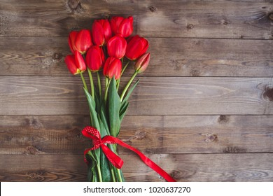 Spring flowers. Bouquet of Red tulips on brown wooden background. Mother's Day and Valentines Day background