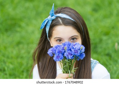 Spring flowers bring new life. Little child hold flowers outdoors. Beauty look of small child. Flower shop. Summer time. Holiday celebration. Flowers and gifts for her. Blooming to life.