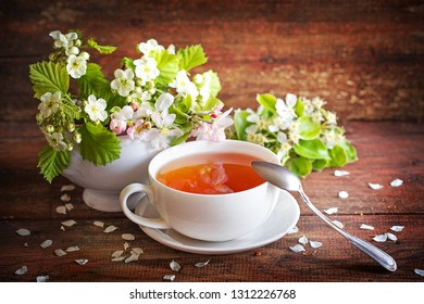 spring flowers brunches and cup of tea on wooden table