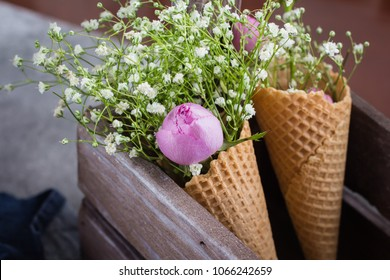 Spring Flowers Card Concept. Gypsophila flowers and pink rose in Waffle cone in wooden box. Mother's Valentine Woman Day Concept.