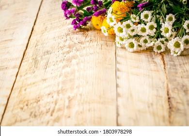 Frühlingsblumen und Kamillen auf Holztisch
