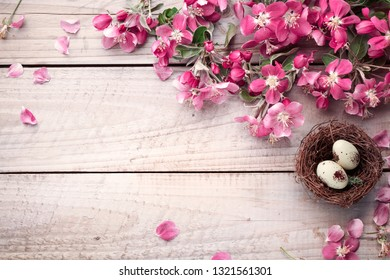 Spring flowers and easter eggs on wooden background