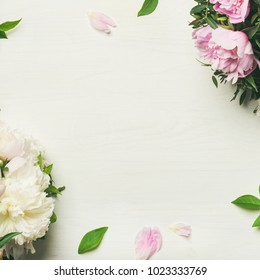 Spring flowers layout. Flat-lay of tender pale pink and white peonies over white background, top view, copy space, square crop. Womens, Valentines or lovers day greeting card or wedding invitation